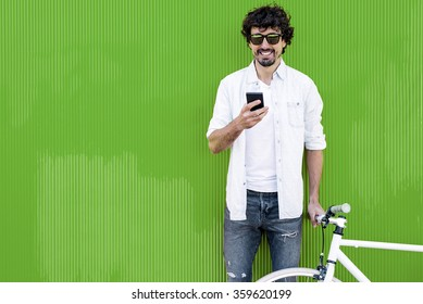 Outdoor portrait of handsome young man with mobile phone and fixed gear bicycle in the street