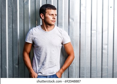 Outdoor portrait of a handsome young man in jeans and gray t-shirt.