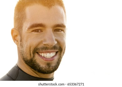 Outdoor portrait of an handsome young surfist smiling