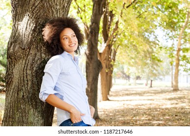 Outdoor portrait of happy beautiful african american woman in nature, female in blue shirts enjoy summer day,  leaning on tree in park, looking at the side