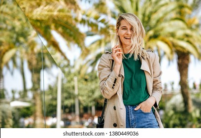 Outdoor portrait of happy beautiful blonde woman smiling broadly, during the journey. Pretty female walking on the city street and relaxing on sunny day, against palms background with copy space.