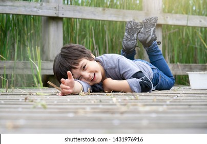 Outdoor portrait of happy boy lying on wooden bridge and looking at camera with smiling face,Active child having fun playing in wildlife park,Kid having adventure in nature reserve in sunny day summer