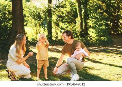 Outdoor-Porträt von glücklicher Familie Spaß im Sommer Park, junge Paar mit Kleinkind Junge und Mädchen