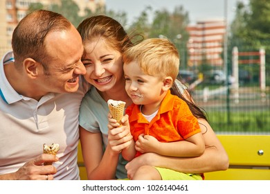 outdoor portrait of a happy family. Mom, dad and child eating ice cream