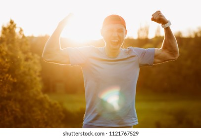 Outdoor portrait of happy fit male athlete enjoying victory in the marathon. Handsome runner looking excited after winner a running race in mountain, raise hands up and clench fits. Sport and people