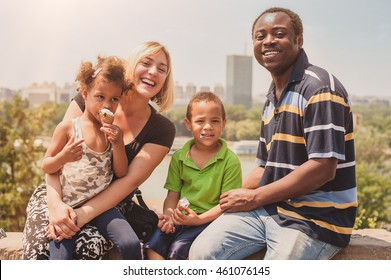 Outdoor portrait of happy international family enjoying and having fun while children eat ice cream cornet in front of city panorama