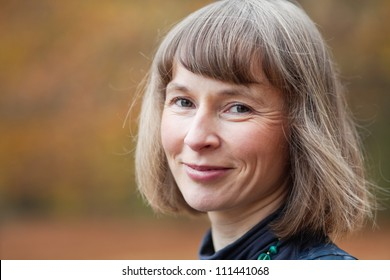 Outdoor portrait of happy middle aged woman in an autumn park