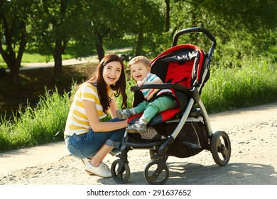 outdoor portrait of a happy mother and son. baby sitting in stroller and mom walk in the summer park