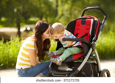 outdoor portrait of a happy mother and son. baby sitting in stroller and mom walking in the summer park