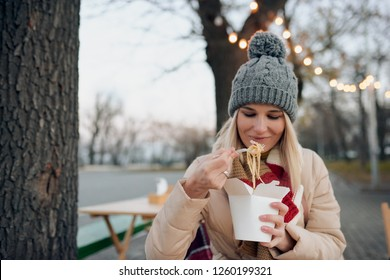 Outdoor portrait of happy pretty woman eating asian wok fast food from takeaway white paper box at the city street. Student female or worker have a lunch break delicious wok noodles in cold wheather.