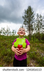 Outdoor portrait of a happy smiling little boy wearing a bib and holding a red soda can. Forest nature scene.