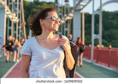 Outdoor portrait of a happy smiling mature woman in sunglasses walking on bridge, golden hour, summer season