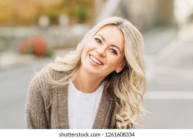 Outdoor portrait of happy smiling woman with blonde hair