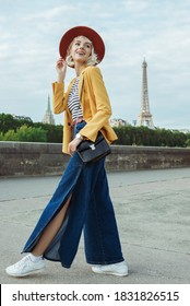 Outdoor portrait of happy smiling woman wearing stylish autumn outfit: orange hat, yellow blazer, wide leg blue jeans, white sneakers, posing in street of Paris