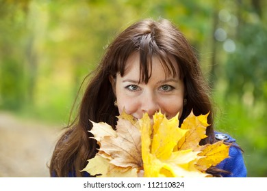 Outdoor portrait of happy woman in autumn with maple posy