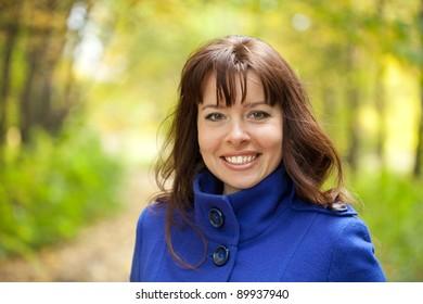 Outdoor portrait of happy woman in autumn