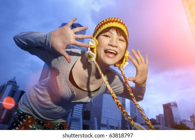 Outdoor portrait of happy young Asian woman in trendy knitted hat with palms open. Twilight city and blue sky as background.