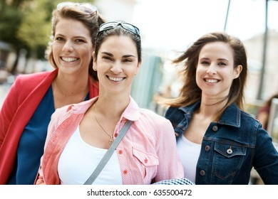 Outdoor portrait of happy young female friends.