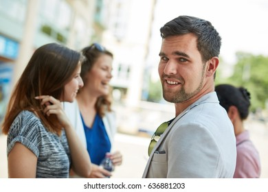 Outdoor portrait of happy young man meeting girls on the street.