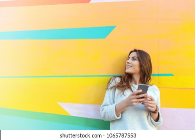 Outdoor portrait hipster woman using a smart phone against colorful street wall
