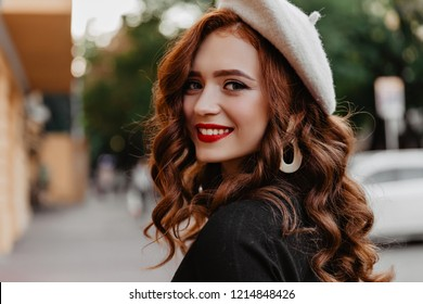 Outdoor portrait of laughing ginger woman with red lips enjoying autumn morning. Debonair french lady in beret looking back.