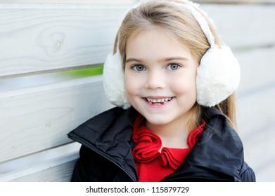 Outdoor portrait of little girl wearing white earmuffs