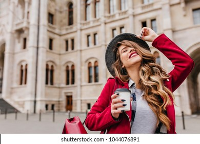 Outdoor portrait of magnificent girl with leather backpack laughing on blur architecture background. Refined young woman with wavy hairstyle having fun during travel around european city.