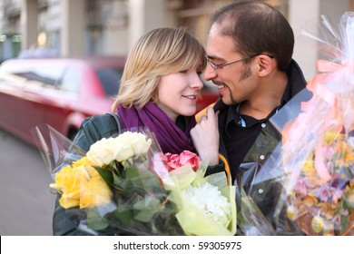 outdoor portrait of man in glasses and beauty blond girl with flower bouquets, looking to each other