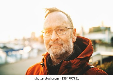 Outdoor portrait of middle age man wearing eyeglasses and orange winter jacket