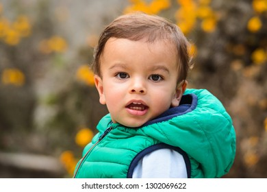 Outdoor portrait of mixed raced toddler in a garden, out of focus marigold flowers in the background.