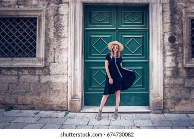 Outdoor portrait of model woman in fashionable black dress,and stylish round sunglasses and yellow hat.Female fashion concept.Retro and vintage filter and colors effect used.