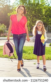 Outdoor portrait of mother and child going to school. Girl 6, 7 years old with glasses, school uniform and happy mom holding hands, back to school
