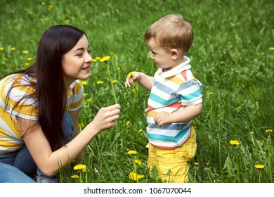 outdoor portrait of a mother with her child. Mom and son walking in a summer park on the grass with yellow dandelions