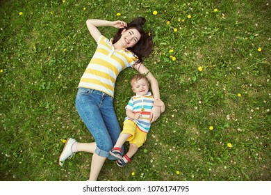 outdoor portrait of a mother with her child. Mom and son walking in a summer park on the grass with yellow dandelions. top view