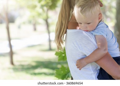 Outdoor portrait of mother and sad crying son in summer park
