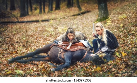 Outdoor portrait of northern viking warrior women with braided hair and painted faces with their horse laying on ground stalking prey on raid using forest as element of surprise to their advantage