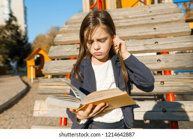 Outdoor portrait of offended little girl. A girl is reading thick book, offendedly pouting her lips.