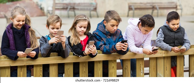 Outdoor portrait of positive european girls and boys playing with phones