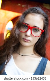 Outdoor portrait of pretty girl with red glasses in park
