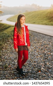 Outdoor portrait of pretty girl wearing red jacket, fashion kid model