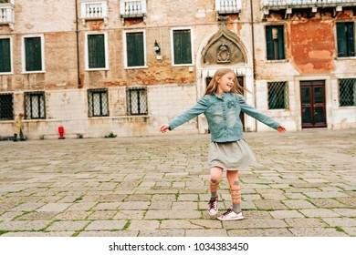 Outdoor portrait of pretty kid girl walking through old italian streets, child dancing outside.
