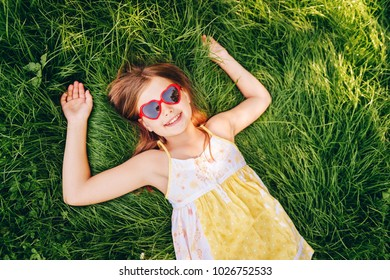 Outdoor portrait of pretty little girl wearing heart shaped sunglasses, lying on fresh green grass. Party for children, summer fun, happy childhood. Top view