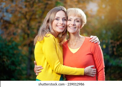 Outdoor portrait of  Pretty smiling Aged Mother and Adult Daughter Portrait Hugging in the autumn Park looking at camera