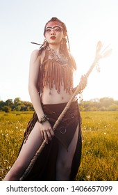 Outdoor portrait of the pretty young shamaness (witch doctor) with staff. Lovely shaman (sorceress) in the field