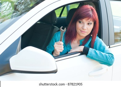 Outdoor portrait of puzzled red-haired young woman sitting in her car with a screw key