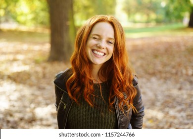 Outdoor portrait of red-haired cheerful woman standing in park on autumn day