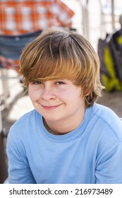 outdoor portrait of relaxed cute young boy looking positive and friendly
