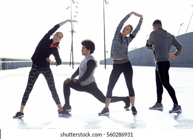 Outdoor portrait of running people doing stretching in the city.