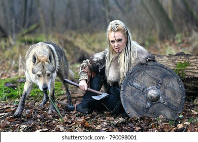 Outdoor portrait of ruthless northern warrior woman with blonde hair in a traditional clothes with fur collar, war makeup, shield and ax, with wolf, forest background