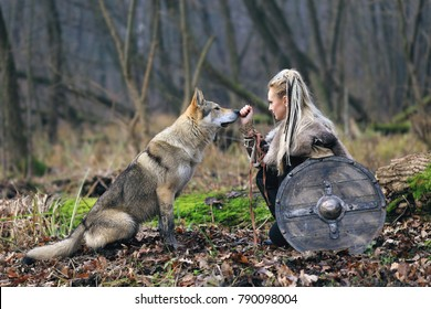 Outdoor portrait of ruthless northern warrior woman with blonde hair in a traditional clothes with fur collar, war makeup, shield and ax, caressing wolf, forest background